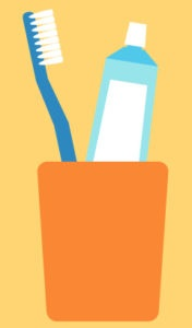A soft-bristled toothbrush and tube of toothpaste in an orange cup against a yellow background to prevent periodontal disease