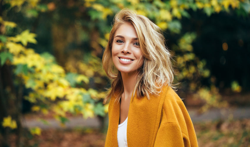Blonde woman smiles free of periodontal disease while outside in the fall foliage