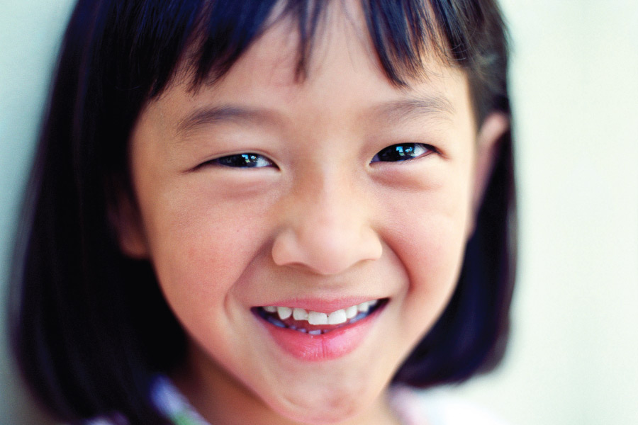 Closeup of a little Asian girl smiling in Forest Hill, TX, after her visit to the dentist